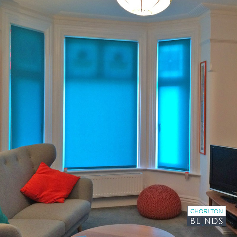Blue dimout roller blinds in bay window