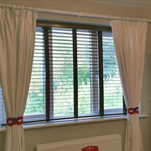 Curtains and wooden venetian blinds in child's bedroom in Chorlton